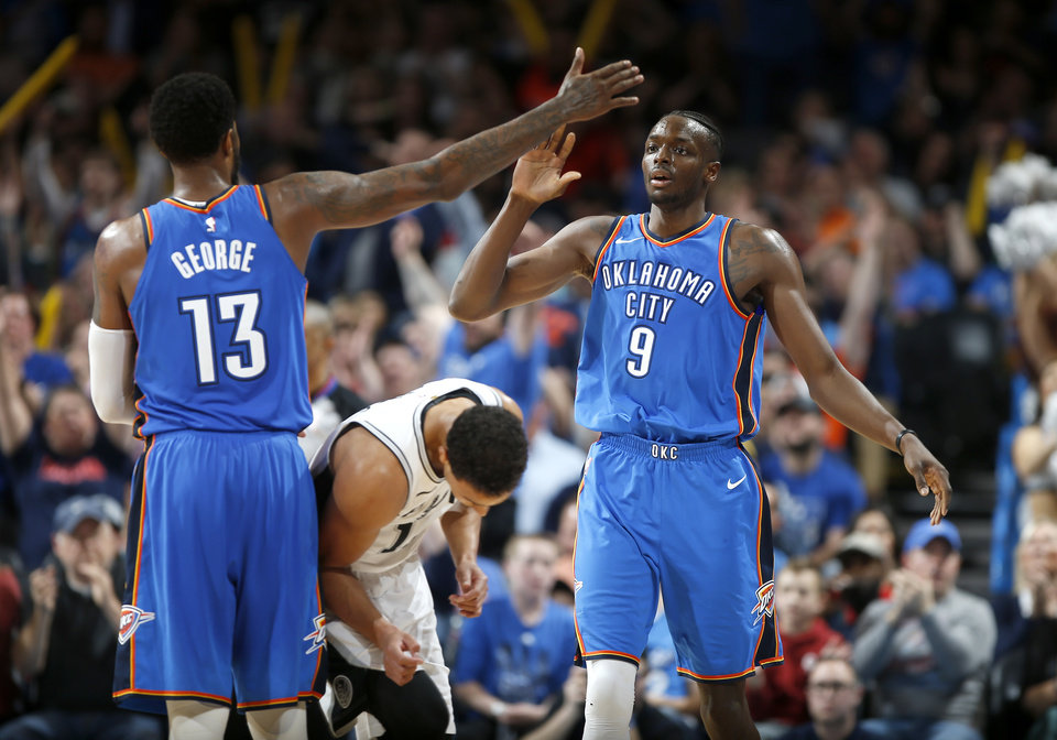 Photo - Oklahoma City's Jerami Grant (9) celebrates with Paul George (13) after making a 3-pointer during an NBA basketball game between the Oklahoma City Thunder and the San Antonio Spurs at Chesapeake Energy Arena in Oklahoma City, Saturday, March 10, 2018.  Photo by Bryan Terry, The Oklahoman