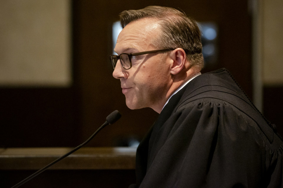 Photo - Judge Thad Balkman reads a summery of his decision in the opioid trial at the Cleveland County Courthouse in Norman, Okla. on Monday, Aug. 26, 2019. Judge Balkman ruled in favor of the State of Oklahoma, that Johnson and Johnson pay $572 million to a plan to abate the opioid crisis. The proceeding were the first public trial to emerge from roughly 2,000 U.S. lawsuits aimed at holding drug companies accountable for the nationÕs opioid crisis.  [Chris Landsberger/Pool]