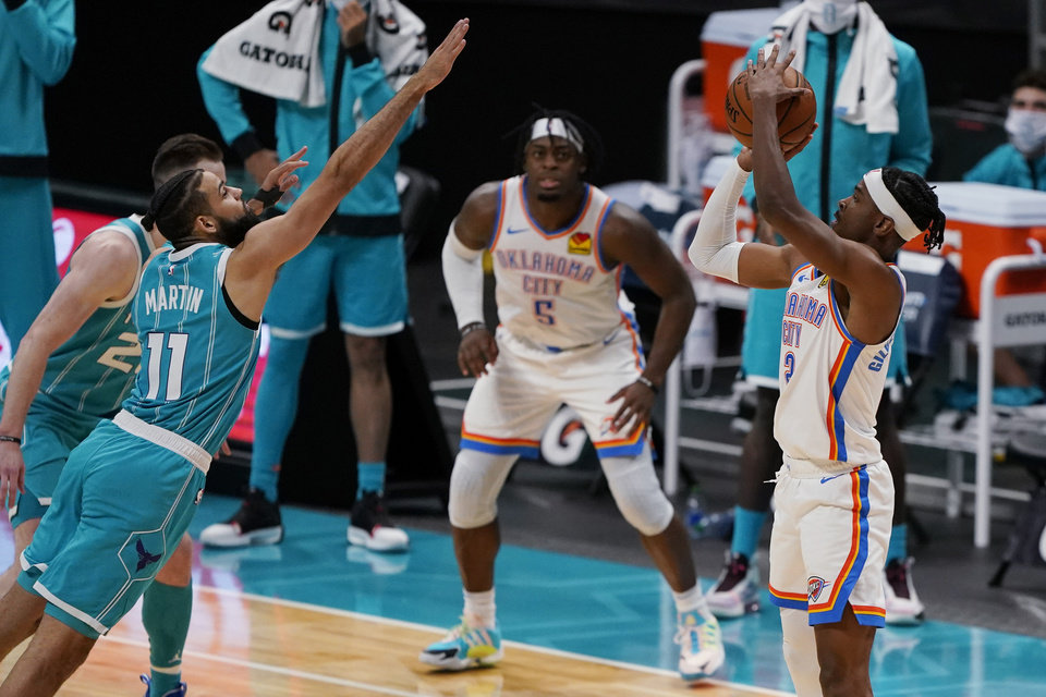 Photo - Oklahoma City Thunder guard Shai Gilgeous-Alexander, right, shoots the go-ahead basket over Charlotte Hornets forward Cody Martin during the second half of an NBA basketball game in Charlotte, N.C., Saturday, Dec. 26, 2020. (AP Photo/Chris Carlson)