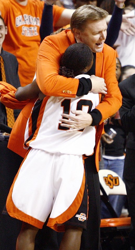 Photo - OSU head coach Kurt Budke hugs Andrea Riley (10) as Riley went to the bench for the final time in the Oklahoma State University Cowgirls and the University of Oklahoma Sooners bedlam women's college basketball game at Gallagher-Iba in Stillwater, Okla., Saturday, January 12, 2008. Riley scored 45 points in OSU's 82-63 win. BY NATE BILLINGS, THE OKLAHOMAN