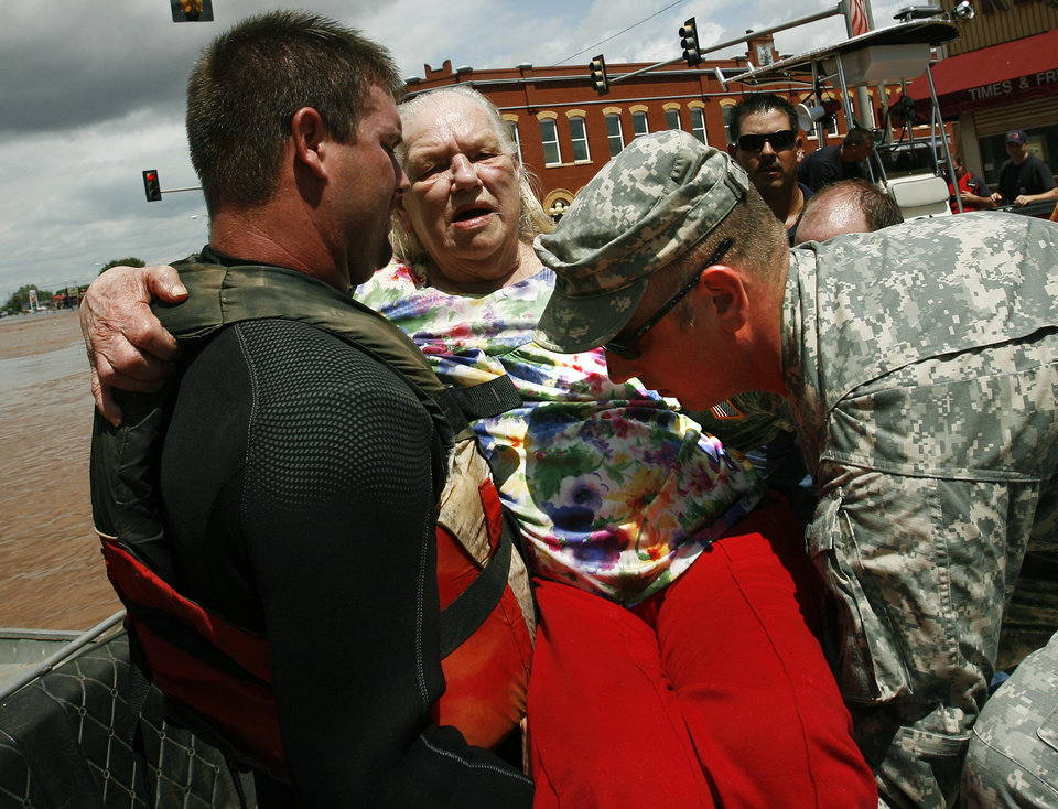 Photo - Margaret Free is lifted from an rescue boat on Sunday, August 19, 2007, in Kingfisher, Okla. after being rescued from her residence. By James Plumlee, The Oklahoman.
