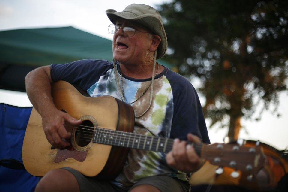 Photo -  Travis Williams, of Tulsa, plays guitar by his camp during the Woody Guthrie Folk Festival in Okemah, Okla., Thursday, July 12, 2012.  Photo by Garett Fisbeck, The Oklahoman
