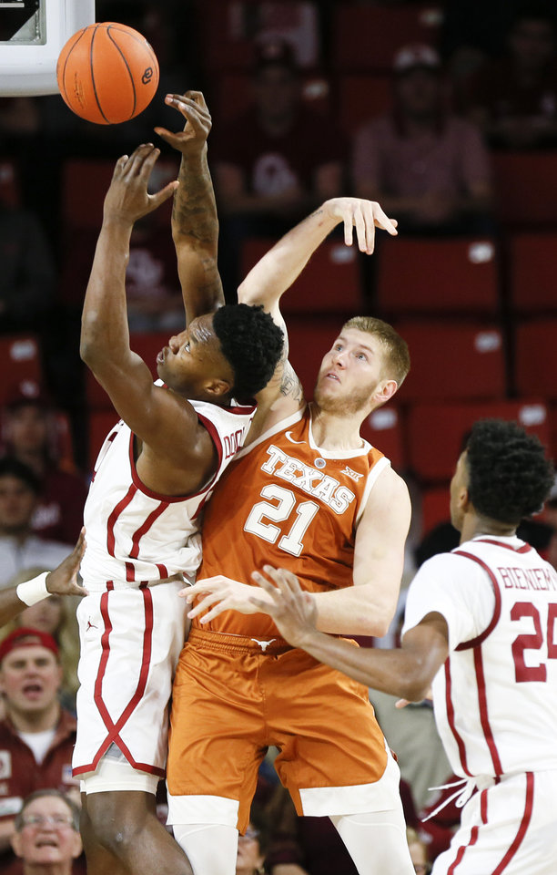 Photo - Oklahoma's Kristian Doolittle (21) and Texas' Dylan Osetkowski (21) try to rebound the ball next to Oklahoma's Jamal Bieniemy (24) during a men's college basketball game between the Oklahoma Sooners and the Texas Longhorns at the Lloyd Noble Center in Norman, Okla., Saturday, Feb. 23, 2019. Oklahoma won 69-67. Photo by Nate Billings, The Oklahoman