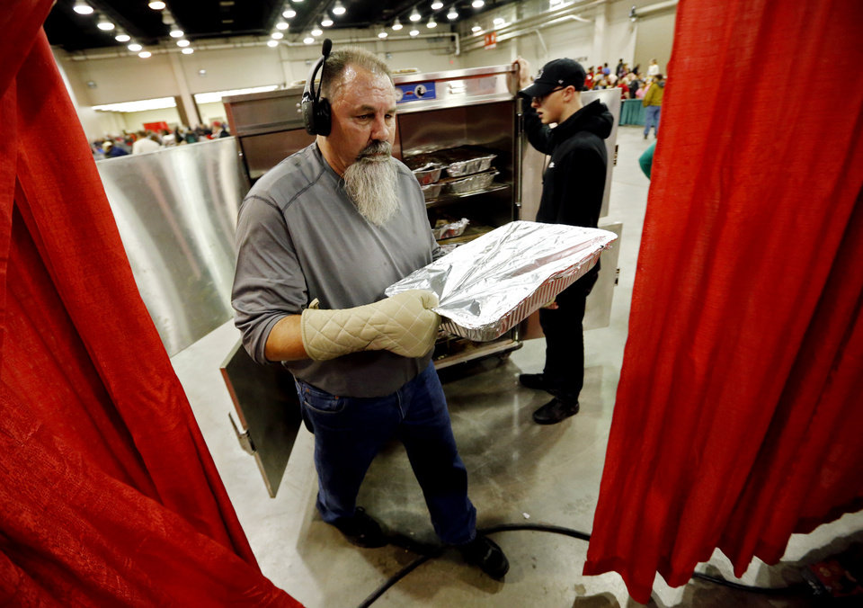 Photo - Kitchen manager Chris Cheffer, left, carries containers of turkey in the food prep area during the annual Red Andrews Christmas Dinner in the Cox Convention Center on Monday, Dec. 25, 2017 in Oklahoma City, Okla.  Cheffer has worked at the event 22 years.  Photo by Steve Sisney, The Oklahoman