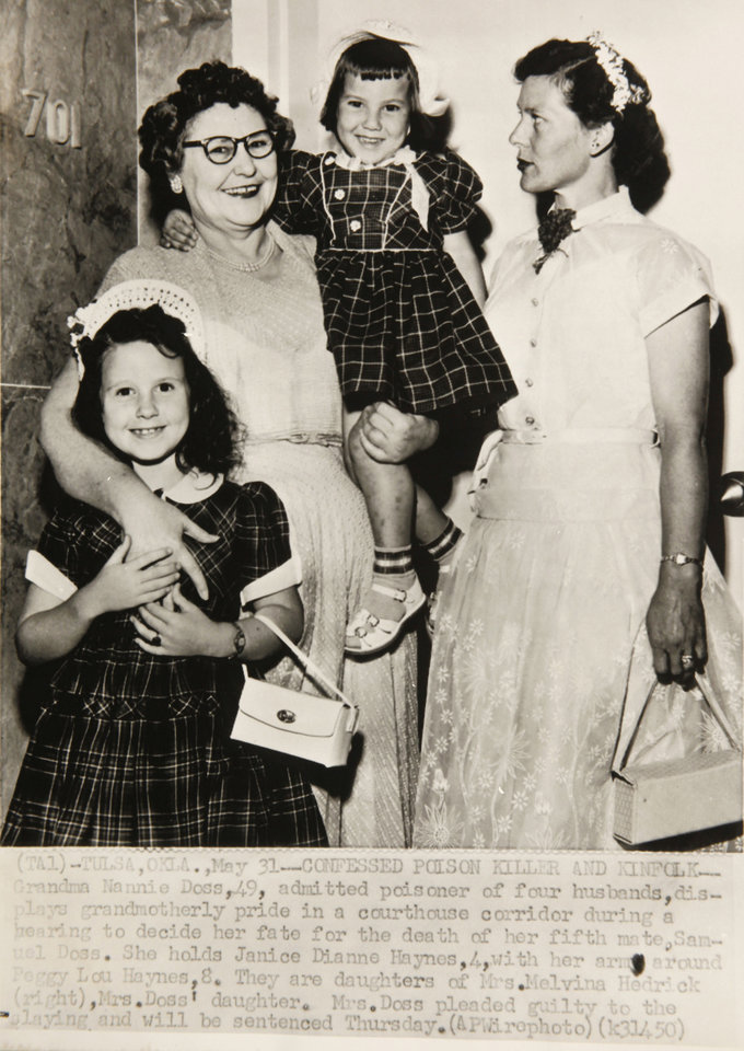 Photo - Nannie Doss, 49, displays grandmotherly pride in a courthouse corridor during a hearing to decide her fate for the death of her fifth mate, Samuel Doss. She holds Janice Dianne Haynes, 4, with her arms around Peggy Lou Haynes, 8. They are daughters of Melvina Hedrick, Doss' daughter.  Oklahoman Archives photo