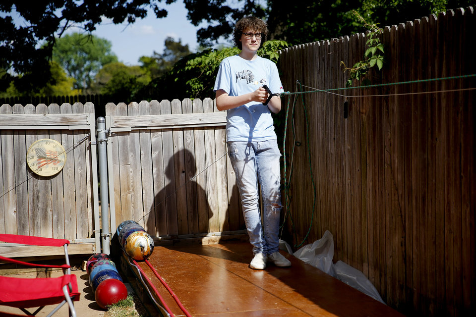 Photo - Eric Jones, 15, pulls a rope to reset bowling pins on a bowling lane in the backyard of his Oklahoma City home, Tuesday, April 21, 2020. Health Jones and his son Eric built a bowling lane in their backyard so that Eric, a competitive bowler, could continue to bowl while bowling alleys are closed.. [Bryan Terry/The Oklahoman]