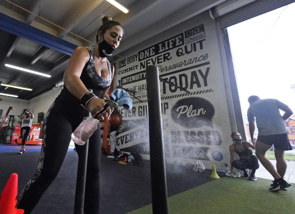 Photo -  Giannina Nicoletti sanitizes a piece of equipment as she works out, Monday, Aug. 31, 2020, at Legacy Fit in the Wynwood Art District of Miami. As the vast majority of in-person fitness clubs switched to virtual classes when the pandemic hit, Legacy Fit took the opposite approach. (AP Photo/Wilfredo Lee)