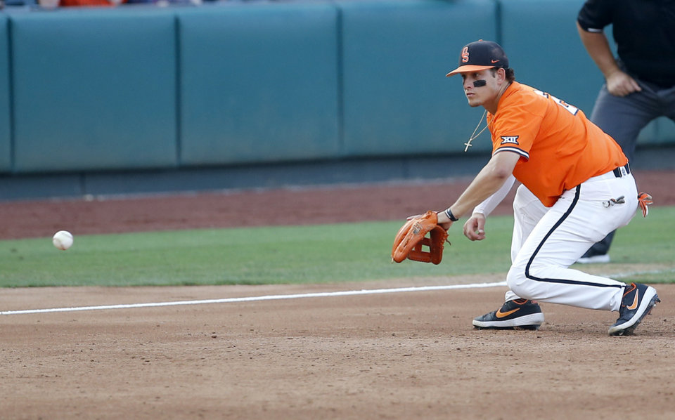 Photo - Oklahoma State's Christian Funk (2) fields a grounder in the 4th inning during the Oklahoma City Regional NCAA baseball game between Oklahoma State University (OSU) and UConn at Chickasaw Bricktown Ballpark in Oklahoma City,  Monday, June 3, 2019. [Sarah Phipps/The Oklahoman]