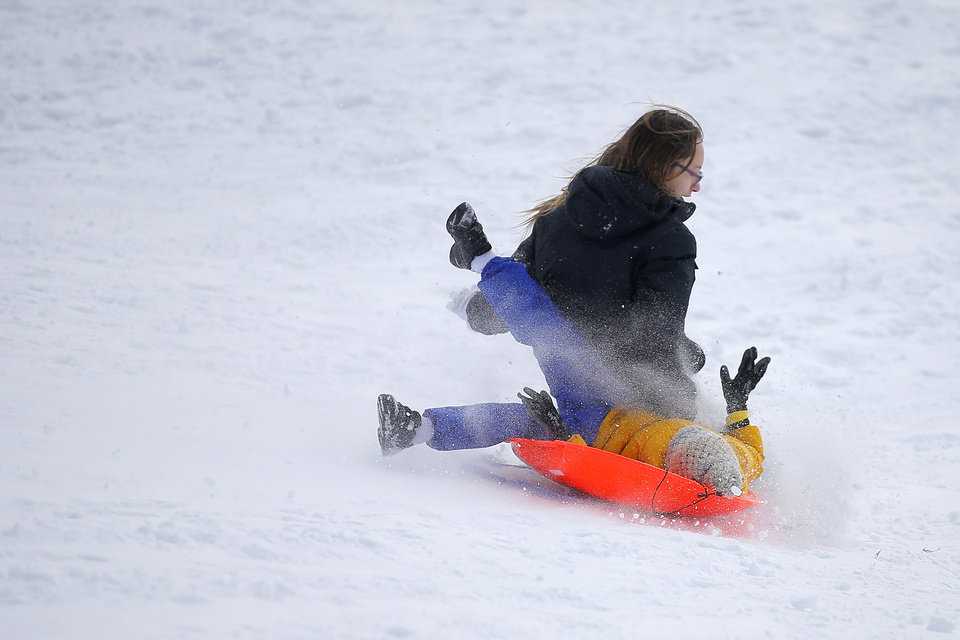 Photo - Teagen Chambers, 12, left, collides with Ali Rhandour, 5, while sledding down a hill along W Hefner Road in Oklahoma City after a winter storm dropped another layer of snow in Oklahoma City, Wednesday, Feb. 17, 2021. [Bryan Terry/The Oklahoman]