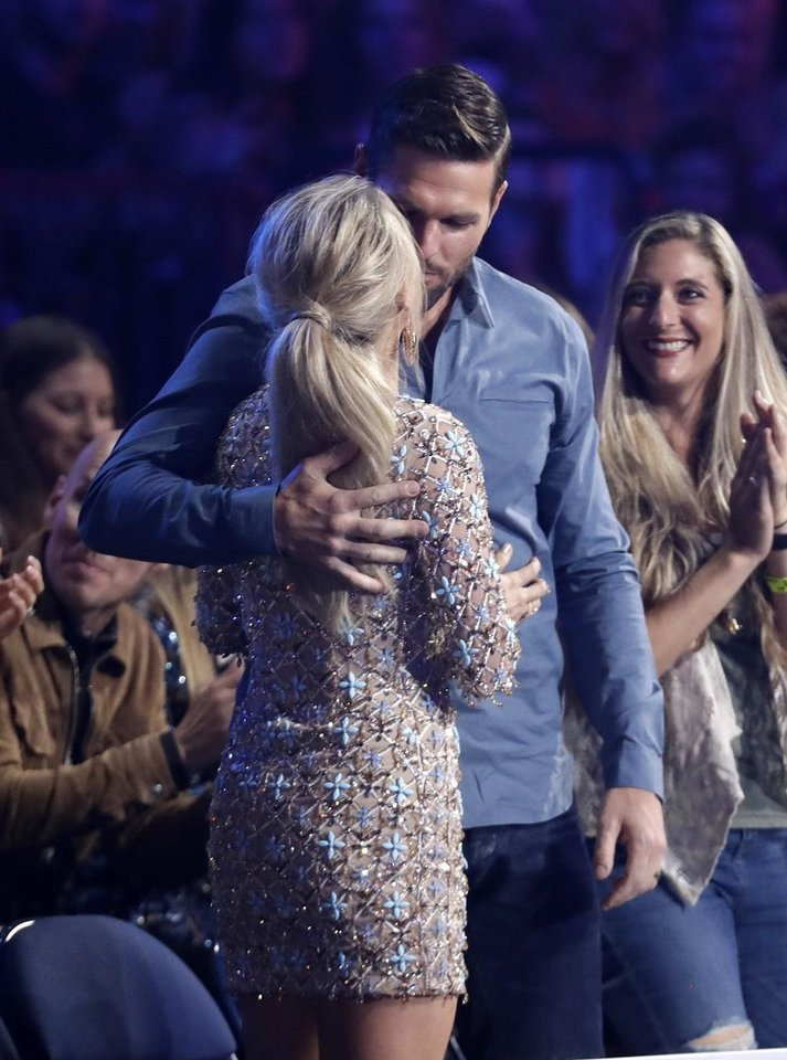 "Photo - Mike Fisher, right, kisses Carrie Underwood, before she goes on stage to accept the award for female video of the year for ""Love Wins"" at the CMT Music Awards on Wednesday, June 5, 2019, at the Bridgestone Arena in Nashville, Tenn. [AP Photo/Mark Humphrey]"
