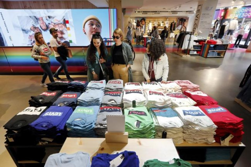 Photo -  A pair of shoppers in the Levi's store in New York's Times Square, survey a T-shirt display. [AP PHOTO]