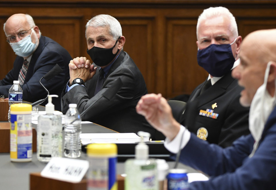 Photo -  From left, Dr. Robert Redfield, director of the Centers for Disease Control and Prevention, Director of the National Institute of Allergy and Infectious Diseases Dr. Anthony Fauci, and Adm. Brett Giroir, head of the U.S. Public Health Service, listen as Food and Drug Administration Commissioner Dr. Stephen Hahn testifies before a House Committee on Energy and Commerce on the Trump administration's response to the COVID-19 pandemic on Capitol Hill in Washington on Tuesday, June 23, 2020. (Kevin Dietsch/Pool via AP)