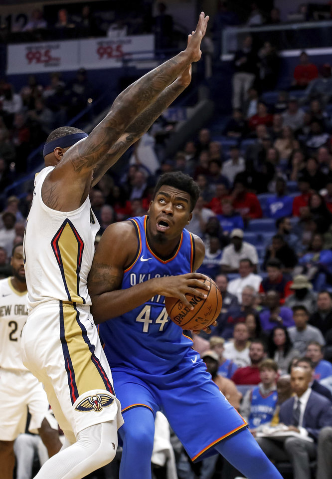 Photo -  Oklahoma City's Dakari Johnson, right, looks for room to shoot against New Orleans' DeMarcus Cousins during Monday night's NBA game at Smoothie King Center in New Orleans. [AP PHOTO]