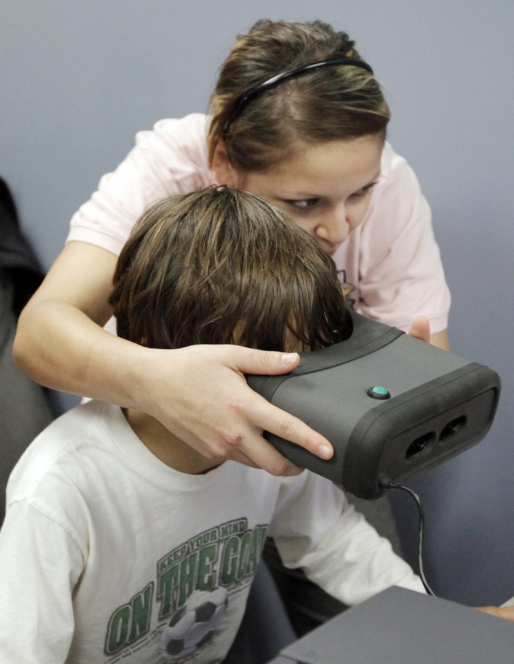 Photo -  Then-administrative assistant Gloria Gomez gives an iris scan in 2009 to a boy at the Oklahoma County Sheriff's substation at the Oklahoma City Zoo. [Photo by Nate Billings, The Oklahoman Archives]