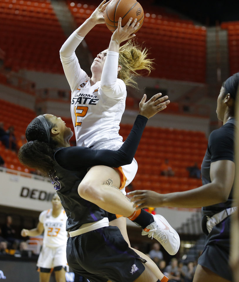 Photo - Oklahoma State's Vivian Gray (12) is called for a foul as she collides with TCU's Jayde Woods (15) during a women's NCAA basketball game between the Oklahoma State University Cowgirls (OSU) and the TCU Horned Frogs at Gallagher-Iba Arena in Stillwater, Okla., Wednesday, Jan. 29, 2020. [Bryan Terry/The Oklahoman]