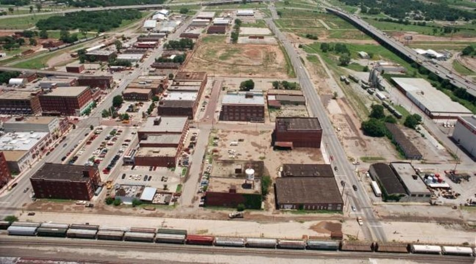 Photo -  Bricktown was a relatively limited destination with about a dozen restaurants and bars as shown in this 1996 photo before construction of the Bricktown Canal and Chickasaw Bricktown Ballpark as part of the original MAPS. The cleared block for the ballpark can be seen in the top center of this photo with California Avenue, the future canal, dead-ended on the west edge of the ballpark site. [The Oklahoman Archives]