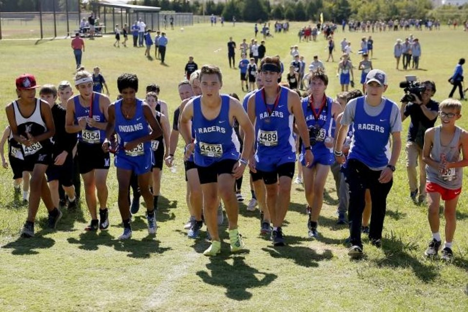 Photo -  Newcastle runner Caleb Freeman, who was injured in a 2017 car crash, is followed by a crowd as he runs a cross country race Tuesday at Carl Albert in Midwest City. [Bryan Terry/The Oklahoman]