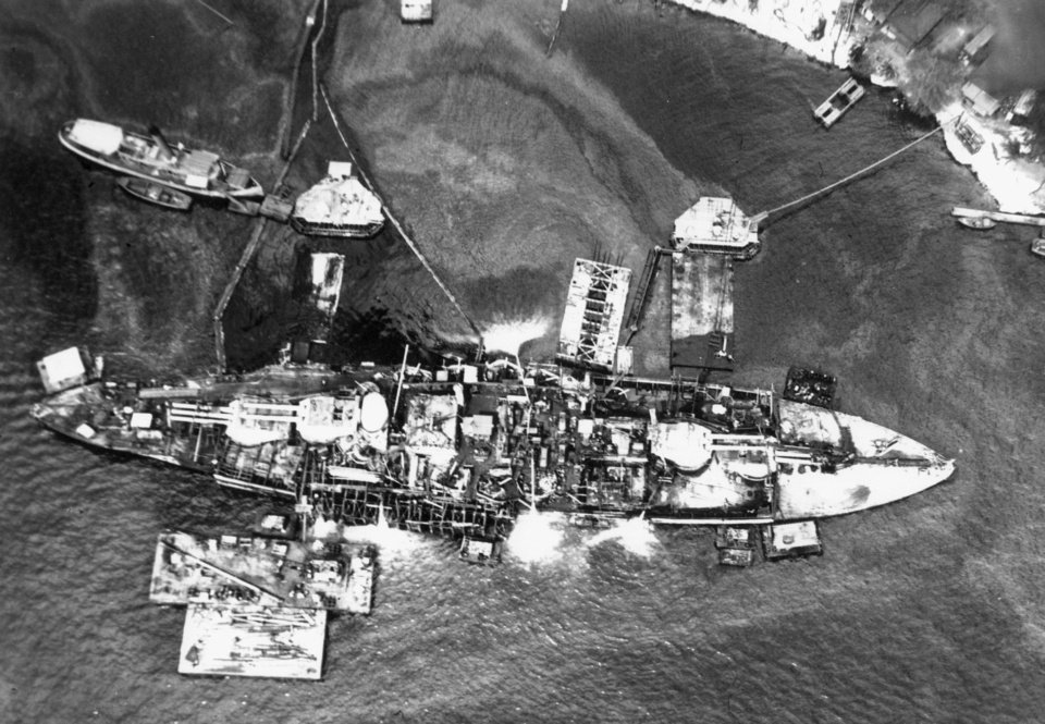 Photo - Rescue crews are shown working in 1943 on refloating of the USS Oklahoma, which was capsized in Pearl Harbor after being blasted by Japanese planes. Holes were burned through the hull to permit the rescue of some men trapped below. The USS Maryland is in the background. U.S. Navy Photo  US NAVY PHOTO: 1943