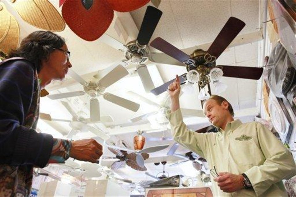 Photo - Jon Reeve, right, manager at Dan's Fan City, shows ceiling fans to a customer in Rockville, Md.,  Wednesday, June 16, 2010.  Ceiling fans can provide an energy-efficient supplement to air conditioning during these hot summer months.    (AP Photo/Jacquelyn Martin)