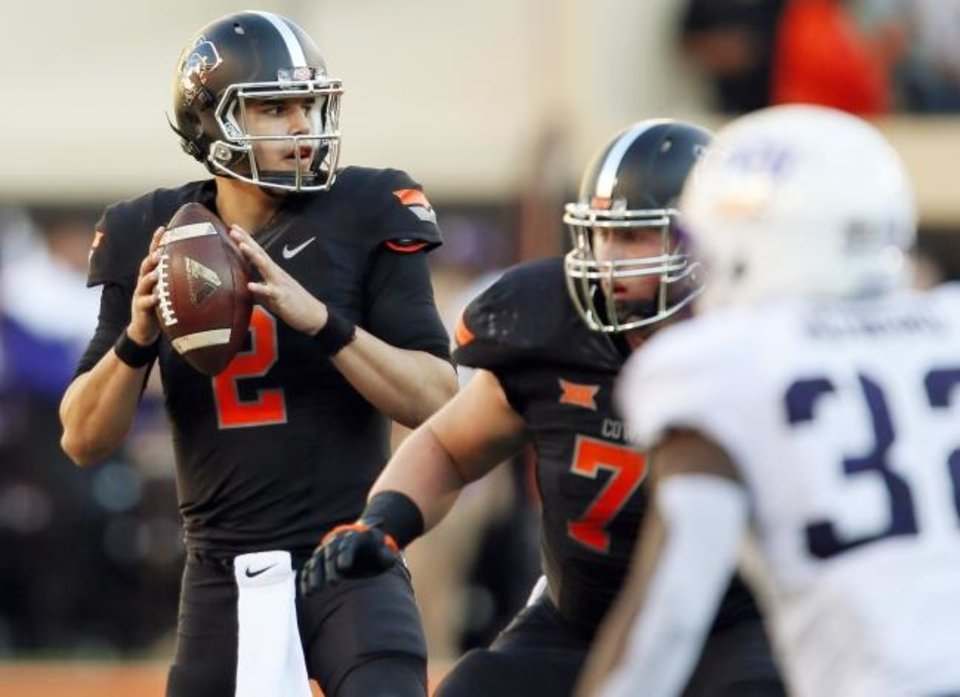 Photo -  The chrome Pistol Pete on matte black helmets make this look the favorite of Oklahoman beat writer Jacob Unruh. Seen here on quarterback Mason Rudolph, the Cowboys wore the all-black look against TCU in 2015. [OKLAHOMAN ARCHIVES]
