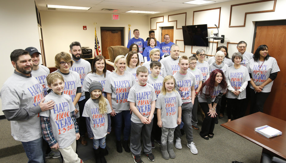 Photo -  Friends and family members pose for photos with Will Yeary, 16, as his adoption is finalized before Judge Cassandra Williams at the Oklahoma Juvenile Justice Center in Oklahoma City. Friends and family members wore