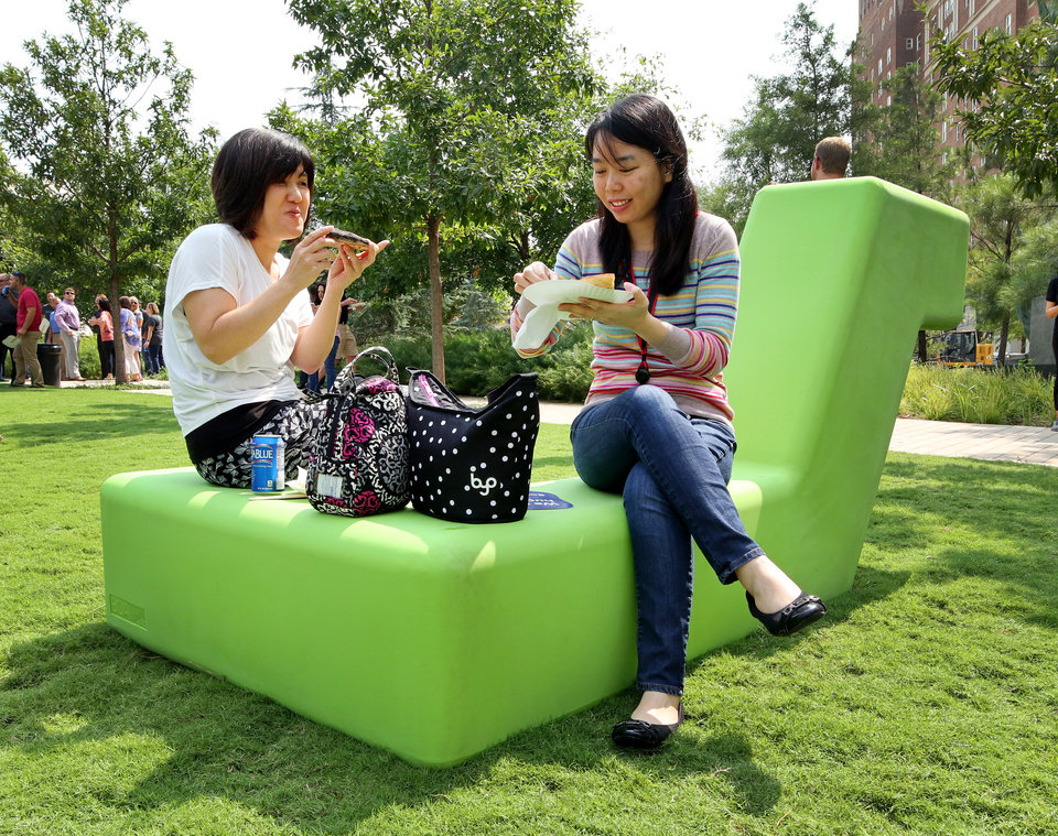 Photo -  Fumiko, left, and Chi Nguyen enjoy lunch on one of the pieces of sculpture furniture during the Kerr Park Kickoff Party on Tuesday.