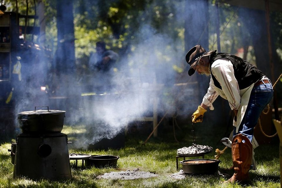 Photo - Chuck wagon cook George Powers makes cobbler during the Chuck Wagon Festival at the National Cowboy & Western Heritage Museum in Oklahoma City, Saturday, May 26, 2018. [Bryan Terry/The Oklahoman Archives]