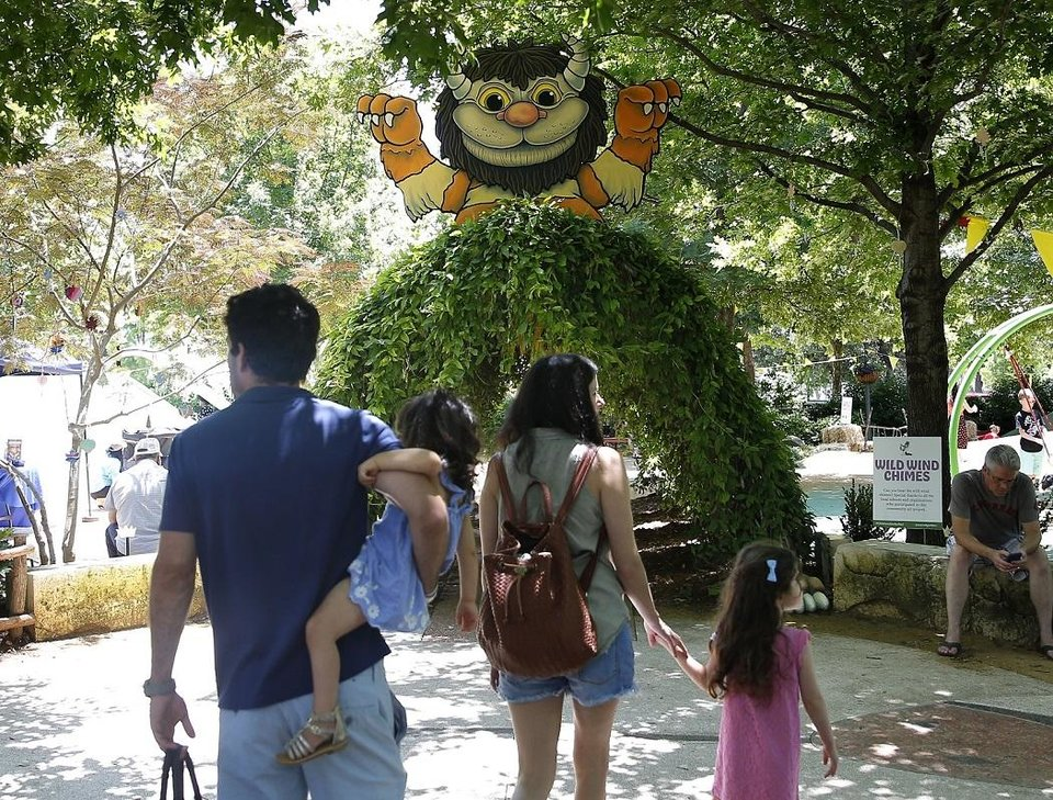 Photo - A family walks in into the Children´s Garden, which is decorated as Where the Wild Things Are as part of 2019 Children´s Garden Festival at the Myriad Gardens in Oklahoma City, Thursday, June 13, 2019. [Sarah Phipps/The Oklahoman Archives]