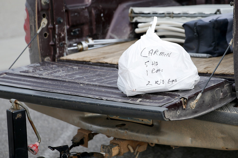 Photo - A food order is seen on the back of a truck  at the Cleveland County Fairgrounds in Norman, Okla., Saturday, March 21, 2020. The weekly Norman Farm Market was closed to walk up business but customers were able to pick up orders placed in advance. [Bryan Terry/The Oklahoman]