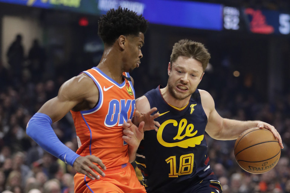 Photo - Cleveland Cavaliers' Matthew Dellavedova (18) drives past Oklahoma City Thunder's Shai Gilgeous-Alexander (2) in the first half of an NBA basketball game, Saturday, Jan. 4, 2020, in Cleveland. [AP Photo/Tony Dejak]
