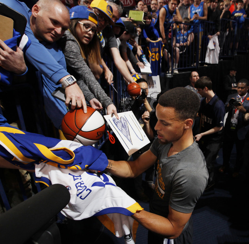 Photo - Golden State's Stephen Curry (30) signs autographs after warming up before an NBA basketball game between the Oklahoma City Thunder and the Golden State Warriors at Chesapeake Energy Arena in Oklahoma City, Saturday, Feb. 27, 2016. Photo by Nate Billings, The Oklahoman