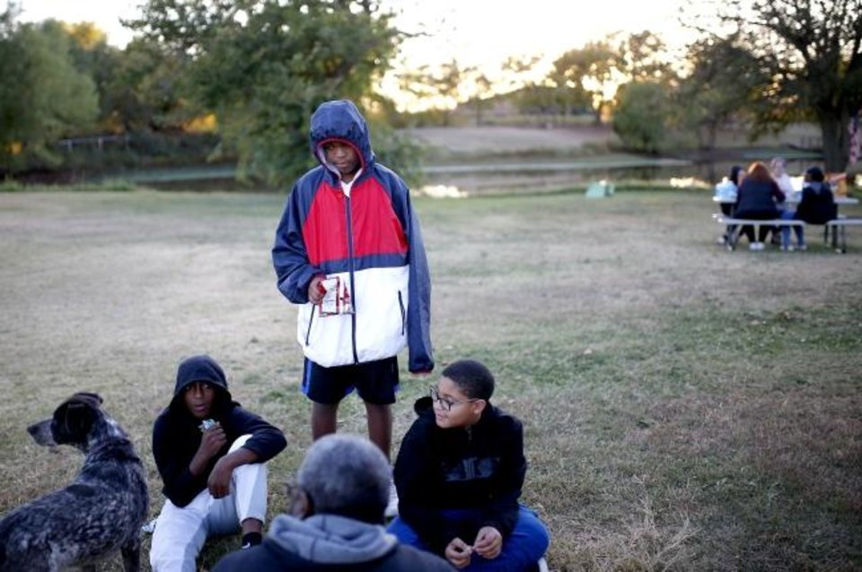 Photo -  From left, Arus Hollins, Steven Matthews and Germond Wills listen to a lesson by mentor Vince Thompson during an outdoors class with Hope for Generations. [Sarah Phipps/The Oklahoman]