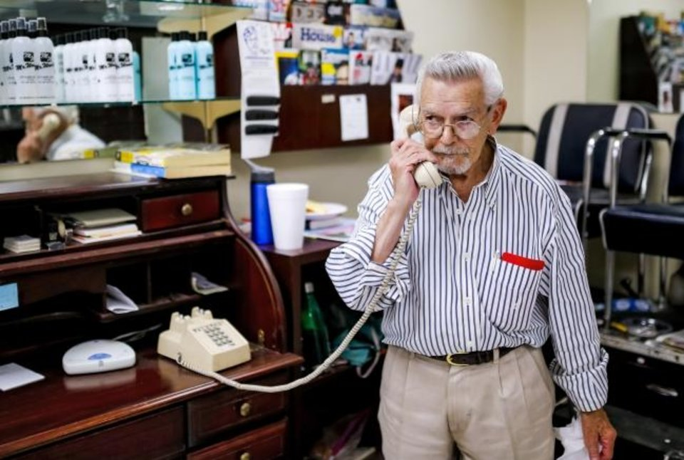 Photo -  Barber Woody Yaklin talks on a phone served by a landline to book an appointment with a client at Woody's Barber and Style Shop in the basement of the State Capitol in Oklahoma City in 2017. Phones served by landlines are becomming less common. [THE OKLAHOMAN ARCHIVES]
