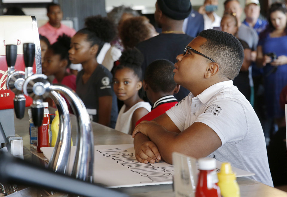 Photo - Sage Walters, 12, right, sits with other children at the counter inside Kaiser's Grateful Bean Cafe to reenact the first Katz Drug Store sit-in, one of the first civil rights protests in the nation, in Oklahoma City, Saturday, Aug. 18, 2018. The sit-in was to commemorate the 60th anniversary of the Katz Drug Store sit-ins. The first Katz Drug Store sit-in happened on August 19, 1958. Photo by Nate Billings, The Oklahoman