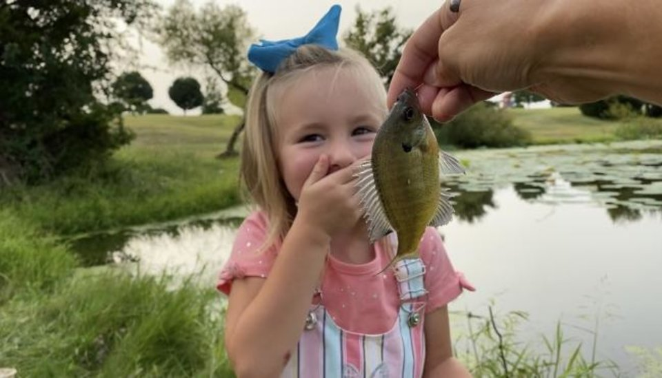Photo -  A young girl reacts to a sunfish that she caught during a fishing clinic for foster children at South Lake Park. [PHOTO PROVIDED BY OKLAHOMA WILDLIFE COSERVATION FOUNDATION]