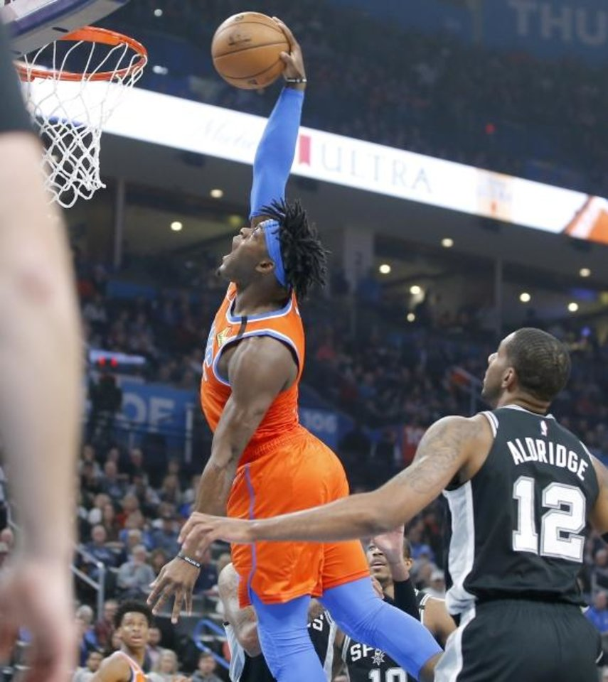 Photo -  Oklahoma City's Luguentz Dort dunks the ball beside San Antonio's LaMarcus Aldridge  during Sunday night's game at Chesapeake Energy Arena. Dort had 15 points to help the Thunder move 13 games over .500. [Bryan Terry/The Oklahoman]