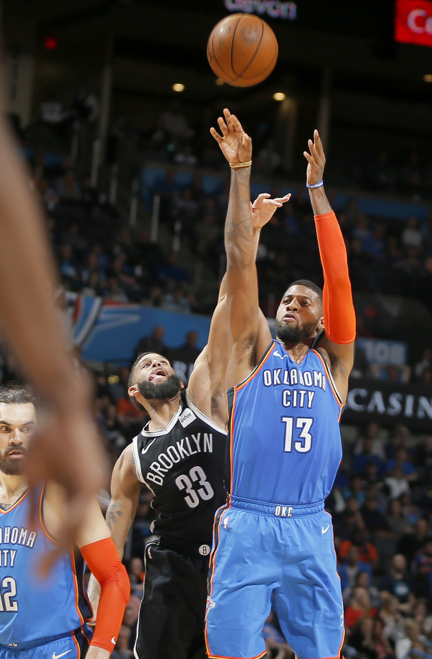 Photo - Oklahoma City's Paul George (13) shoots as Brooklyn's Allen Crabbe (33) defends during an NBA basketball game between the Oklahoma City Thunder and the Brooklyn Nets at Chesapeake Energy Arena in Oklahoma City, Wednesday, March 13, 2019. Oklahoma City won 108-96. Photo by Bryan Terry, The Oklahoman