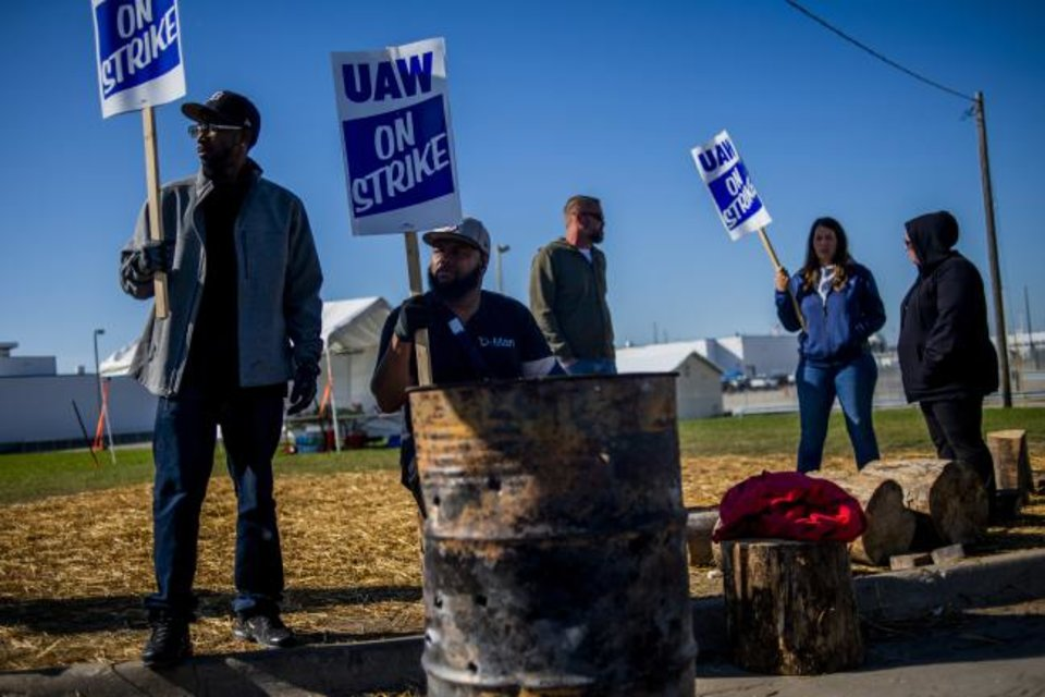 Photo -  Detroit resident Jay Hawkins, left, and Flint resident Damien Moore picket outside of General Motors' Flint Paint Facility during the nationwide UAW strike against General Motors on Monday. [AP PHOTO]