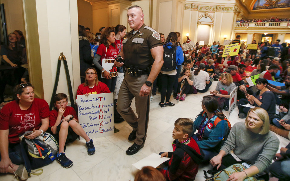 Photo - A state trooper walks by teachers and their supporters as they sit on the fourth floor in front of the entrance to the House of Representatives during the second day of a walkout by Oklahoma teachers at the state Capitol in Oklahoma City, Tuesday, April 3, 2018. Photo by Nate Billings, The Oklahoman