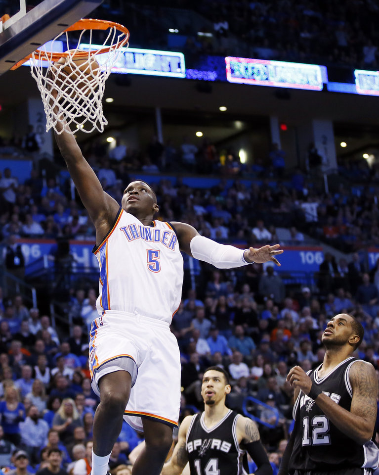 Photo - Oklahoma City's Victor Oladipo (5) takes the ball to the hoop past San Antonio's Danny Green (14) and LaMarcus Aldridge (12) during an NBA basketball game between the Oklahoma City Thunder and San Antonio Spurs at Chesapeake Energy Arena in Oklahoma City, Friday, March 31, 2017. San Antonio won 100-95. Photo by Nate Billings, The Oklahoman