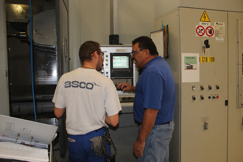 Photo - An ASCO employee at the Belgium facility demonstrates the machining of airplane parts to Meridian Technology Center's Product Development and Machining Instructor Jimmy Williams, right.