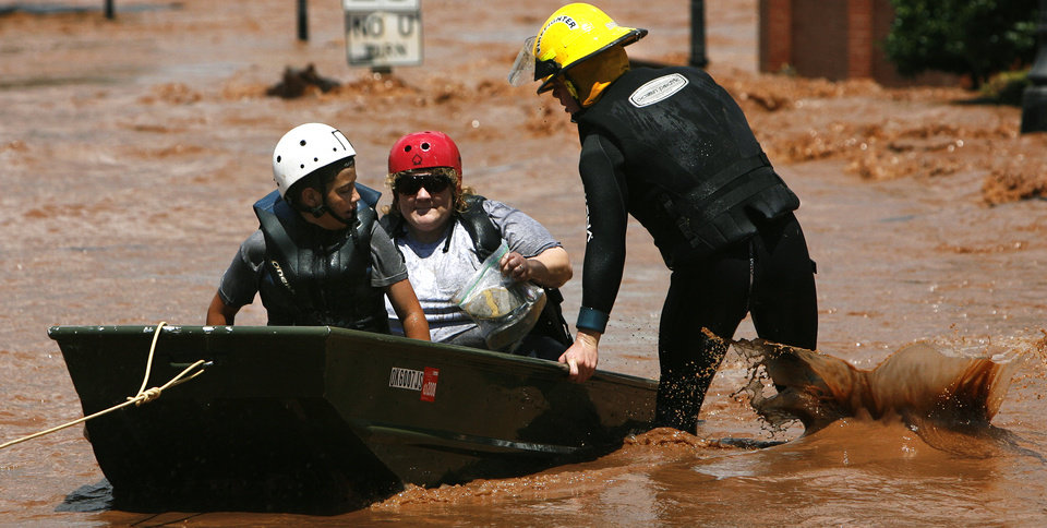 Photo - A firefighter guides a boat containing Grant Borelli and Shawna Crum after the two were rescued from rising floodwaters on Sunday, August 19, 2007, in Kingfisher, Okla. By James Plumlee, The Oklahoman.