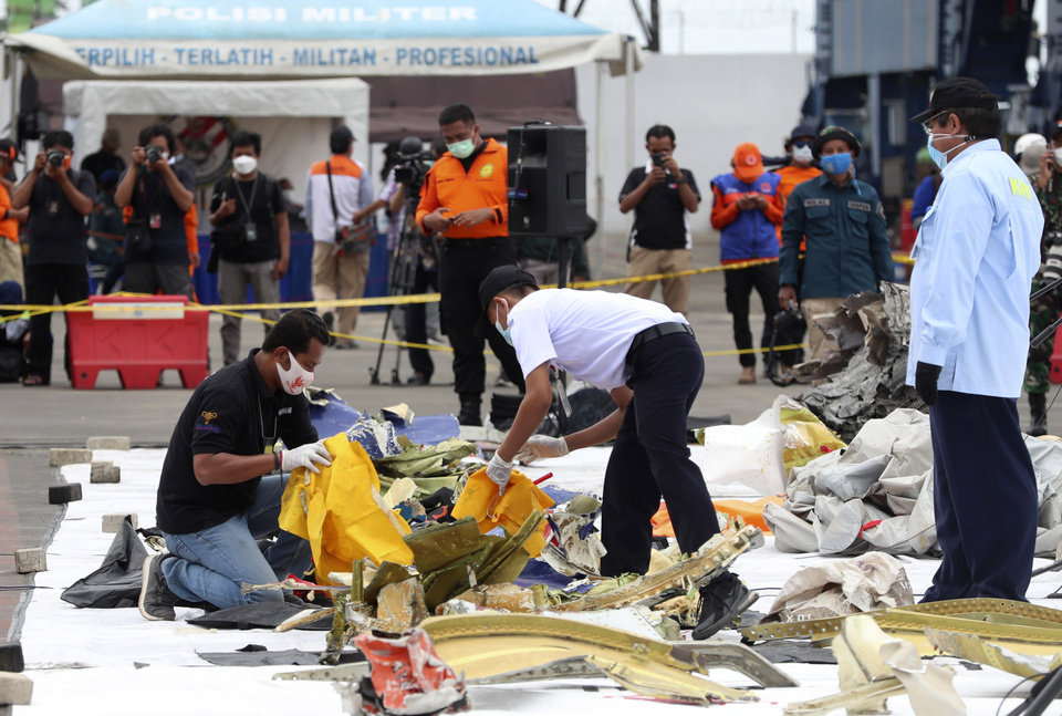 Photo -  Indonesian National Transportation Safety Committee (KNKT) investigators inspect the debris found in the waters around the location where Sriwijaya Air passenger jet crashed at Tanjung Priok Port in Jakarta, Indonesia, Monday, Jan. 11, 2021. The search for the black boxes of a crashed Sriwijaya Air jet has intensified to boost the investigation into what caused the plane carrying dozens of people to nosedive into Indonesia seas. The Boeing 737-500 jet disappeared during heavy rain on Saturday. (AP Photo/Achmad Ibrahim)