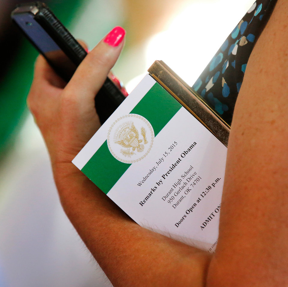 Photo - A woman carries her cell phone and her admission ticket to hear President Barack Obama as he spoke  to about 950 people in Durant's new high school on Wednesday, July 15, 2015.  He used his visit in Durant to announce his administration's newest initiative, ConnectHome. It's described as a cooperative effort with communities, the private sector and federal government  to expand high speed broadband to more families across the country. The pilot program is launching in 27 cities and one tribal nation, the Choctaw Nation in southeast Oklahoma. Photo by Jim Beckel, The Oklahoman.