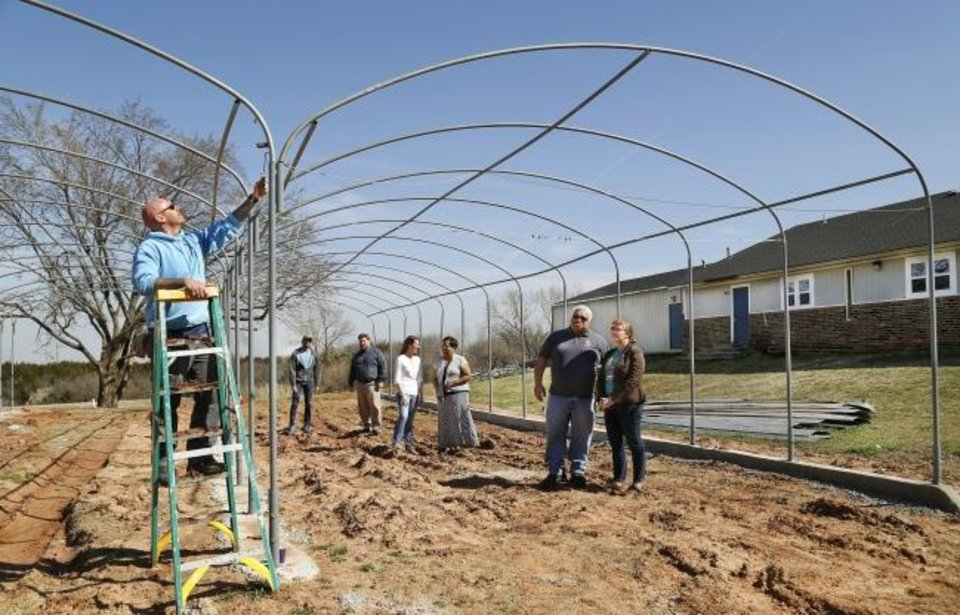 Photo -  Philip Meadows paints the support frame of a green house being constructed behind Restore OKC's office in a former northeast Oklahoma City church. At right are: Micah Anderson, Ann Miller, Caylee Dodson, Keisha Scott, Ernest Odunze and Joshua Ringer. [Jim Beckel/The Oklahoman]