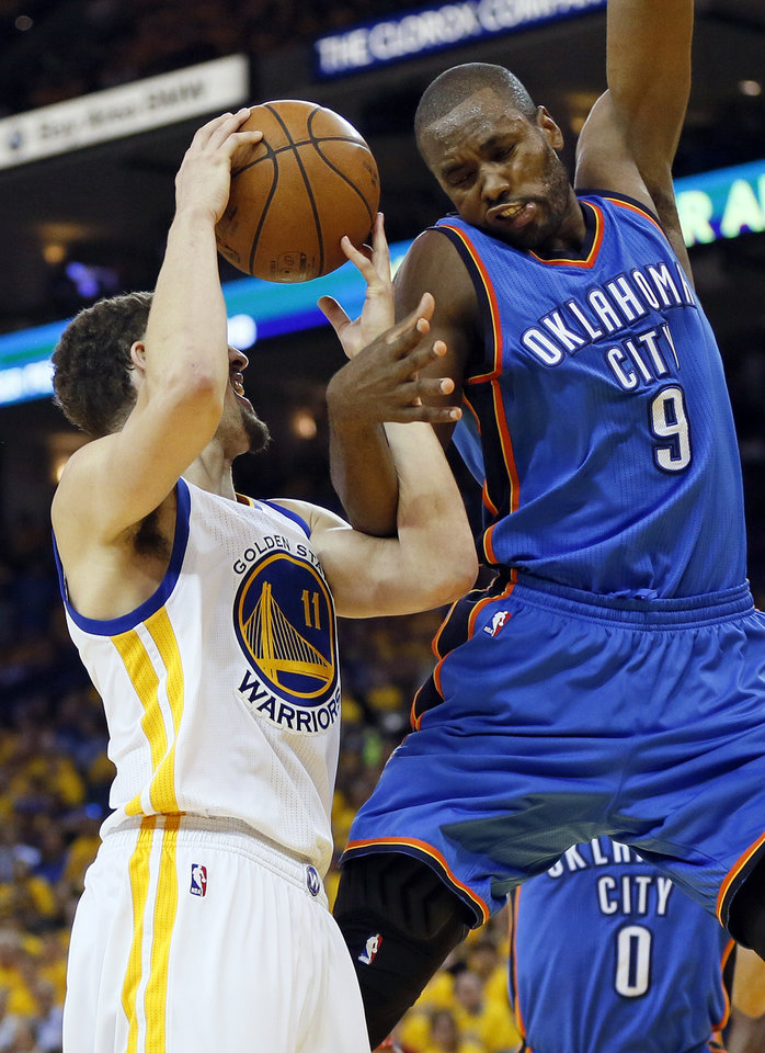 Photo - Oklahoma City's Serge Ibaka (9) fouls Golden State's Klay Thompson (11) in the fourth quarter during Game 2 of the Western Conference finals in the NBA playoffs between the Oklahoma City Thunder and the Golden State Warriors at Oracle Arena in Oakland, Calif., Wednesday, May 18, 2016. Golden State won 118-91. Photo by Nate Billings, The Oklahoman