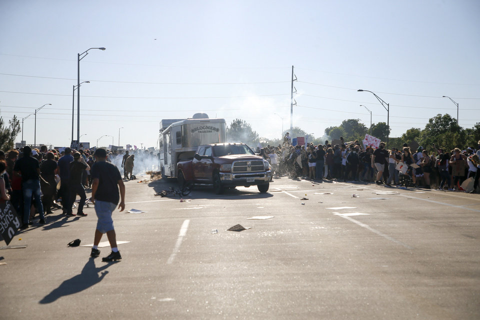Photo - A truck drives through a group of protesters who had shut down Interstate 244 during a rally in Tulsa, Okla., Sunday, May 31, 2020. The march was to mark the anniversary of the 1921 Tulsa race massacre and to protest the death George Floyd, who died May 25 after he was pinned at the neck by a Minneapolis police officer. (Ian Maule/Tulsa World via AP)