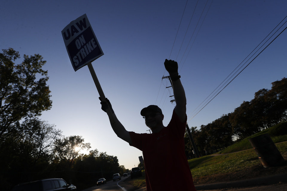 Photo -  A member of the United Auto Workers cheers on honking cars as he walks the picket line at the General Motors Romulus Powertrain plant in Romulus, Mich. [AP PHOTO]