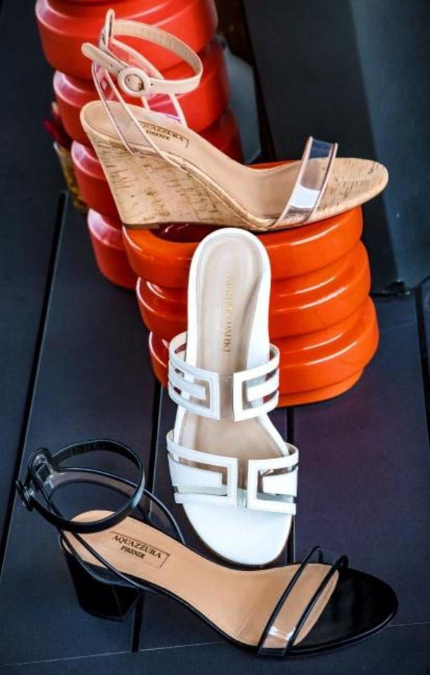 Photo -  Aquazzura chunky heeled sandal with clear straps, $650; Marion Parke white patent slide with clear straps, $495; and Aquazzura wedge ankle strap with clear straps, $625, all from Balliets. [Chris Landsberger/The Oklahoman]