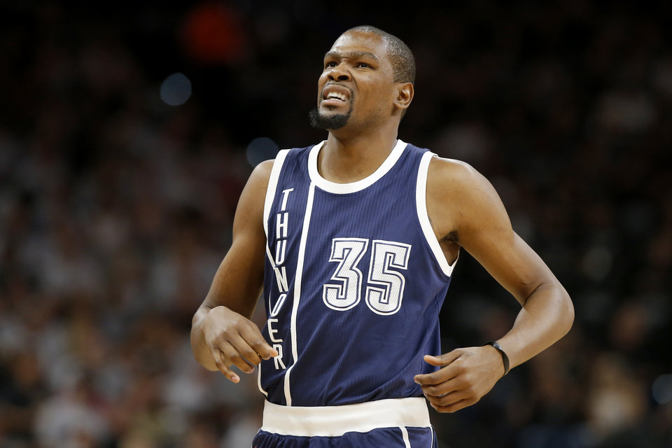 Photo - Oklahoma City's Kevin Durant (35) grimaces as he shakes his hand during Game 1 of the second-round series between the Oklahoma City Thunder and the San Antonio Spurs in the NBA playoffs at the AT&T Center in San Antonio, Saturday, April 30, 2016. San Antonio won 124-92. Photo by Bryan Terry, The Oklahoman